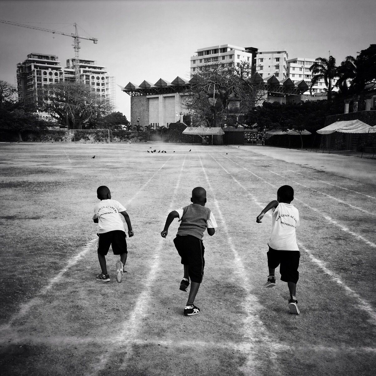 Three boys from the junior school of Aga Khan Academy in Mombasa,Kenya, race on the school's track before the morning assembly. Photo by @austin_merrill.