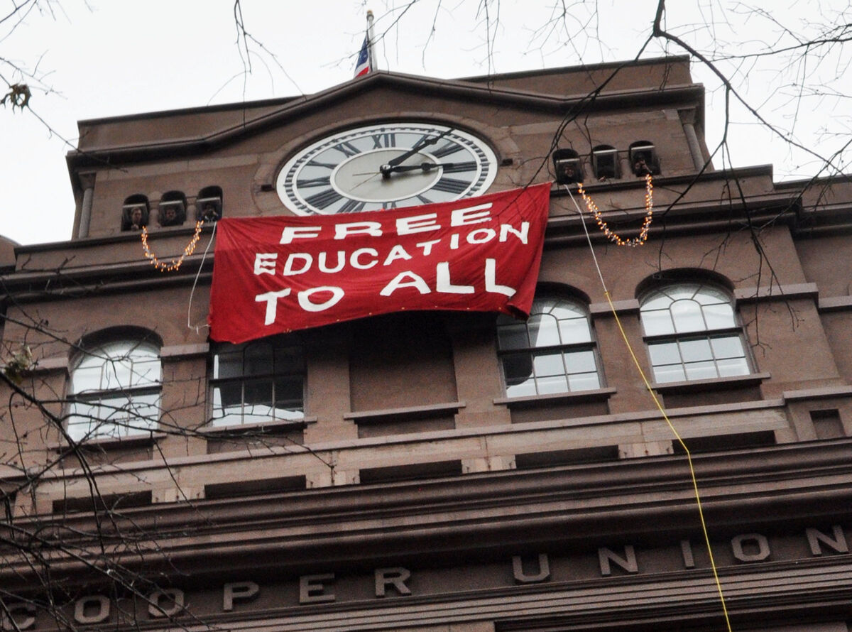 Students hang banner below the historic clock tower of the Cooper Union Foundation building in New York City during a December occupation. Photo by Michael Fleshman.