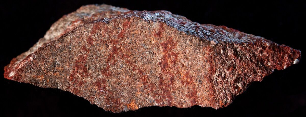 The ocher-marked stone flake recently discovered in Blombos Cave. Photo courtesy and © Craig Foster.