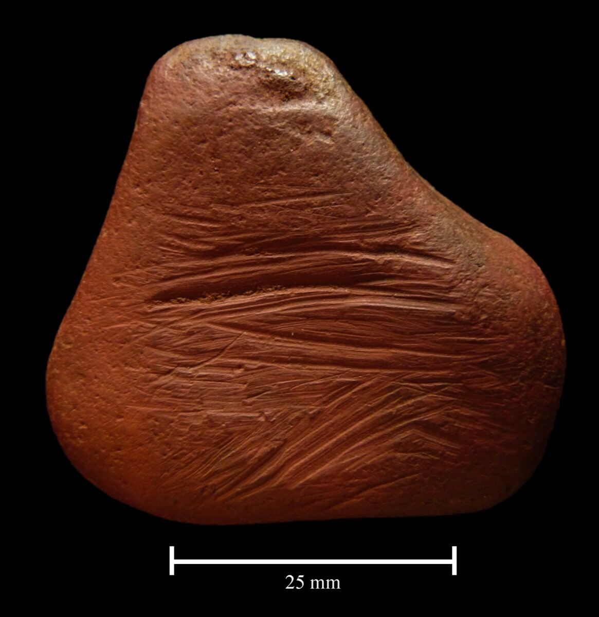 An ochre pebble found at the same site. Courtesy of Paul Shields, University of York.
