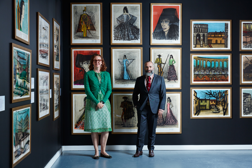 Kelly Troester (left) and Cary Leibowitz (right) pose with a selection of Bernard Buffet lithographs and engravings now on view at 450 Park Avenue