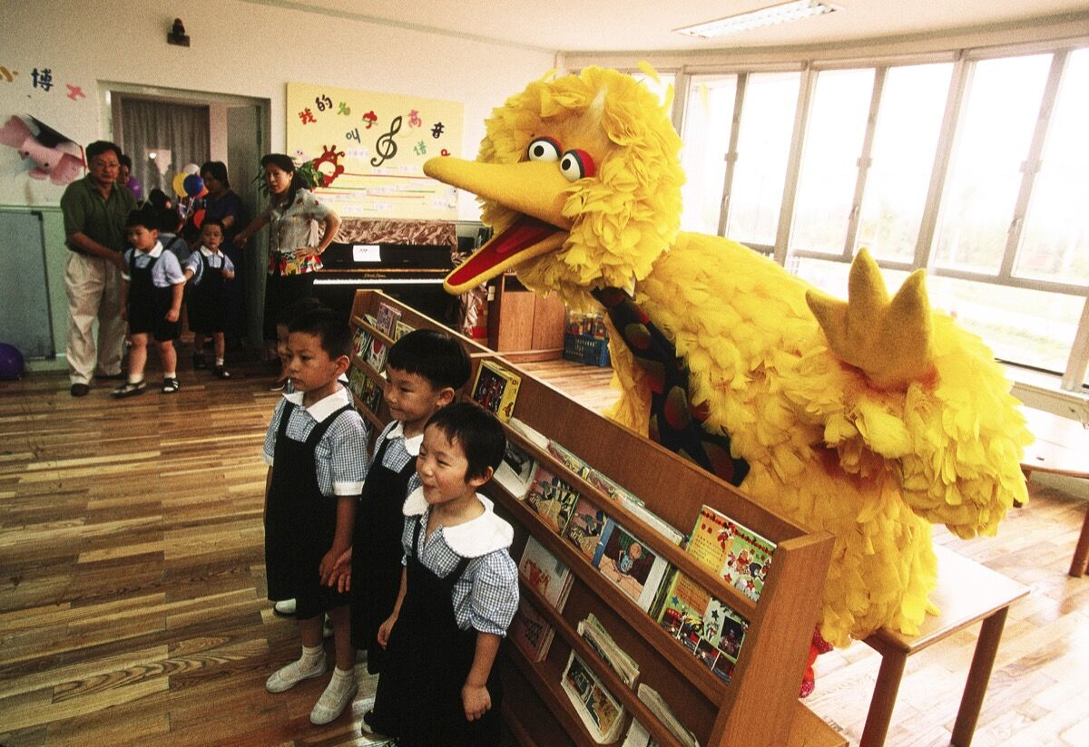 Children pose in class for a photo with Big Bird of Sesame Street. Photo by Joe McNally/Getty Images.