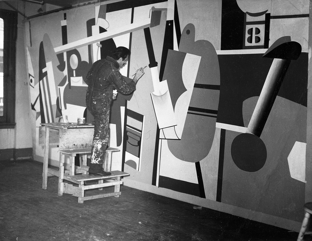 """Arshile Gorky working on one of the panels for his """"Aviation"""" murals for the Newark Airport. Photo viaFederal Art Project, Photographic Division, Smithsonian National Archives of American Art."""