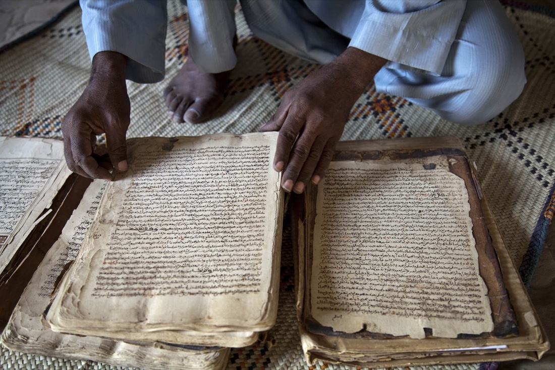 Abdul Wahid shows a manuscript from the 14th century at his house in Timbuktu. Photo by MINUSMA/Marco Dormino, via Flickr.