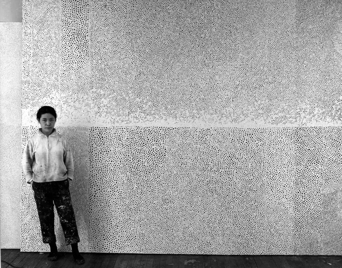"Yayoi Kusama with ""Infinity Net"" paintings in her New York studio, 1961. Image © Yayoi Kusama. Courtesy of David Zwirner, New York; Ota Fine Arts, Tokyo / Singapore; Victoria Miro, London; YAYOI KUSAMA Inc."