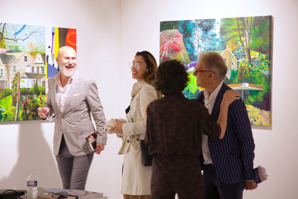 Anca Poterasu (center right, owner of her namesake Bucharest gallery) engages collectors around works by Iulian Bisericaru