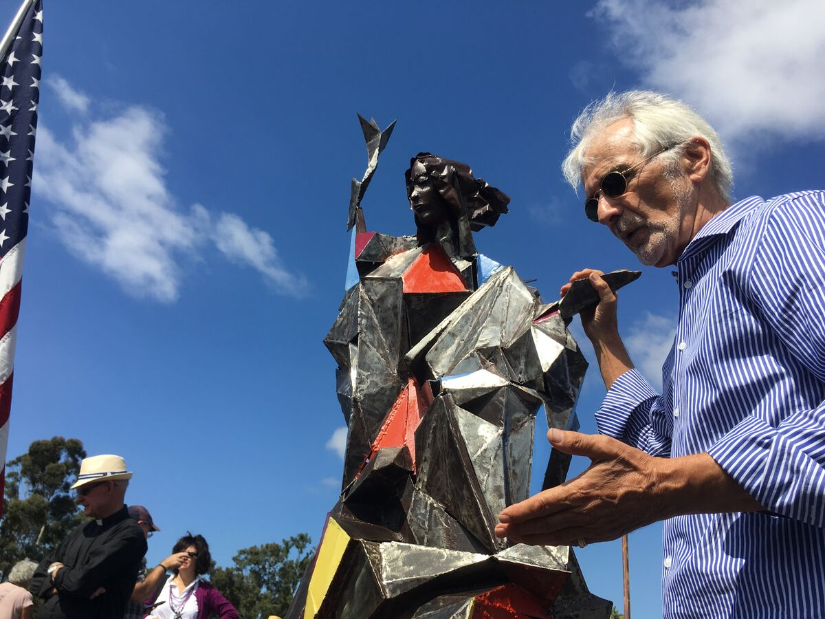 Artist Jim Bliesner with a 4-foot metal model of Welcome the Stranger. Courtesy of the San Diego Organizing Project.