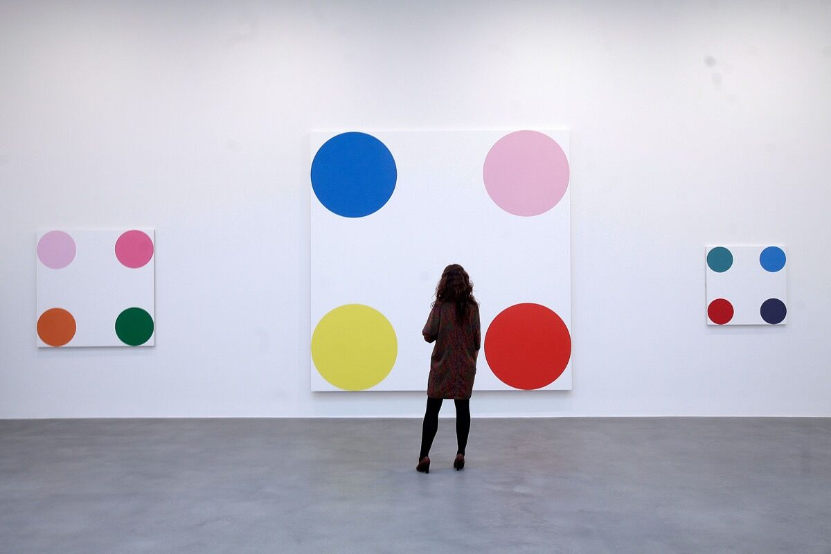 An employee looks at the artwork '4-Chlorephenol, 2008', part of the artist Damien Hirst's exhibition 'The Complete Spot Paintings' at the Gagosian Gallery on January 12, 2012 in London, England.  Photo by Matthew Lloyd/Getty Images.