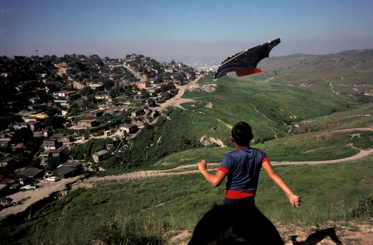 USA. San Ysidro, Ca. Mexican children playing with kite on the U.S. side of the border. (They are in the U.S. illegally.) The houses below them are in Tijuana, Mexico, where they live. Photo by Alex Webb. © Alex Webb/Magnum Photos. Courtesy of Magnum Photos