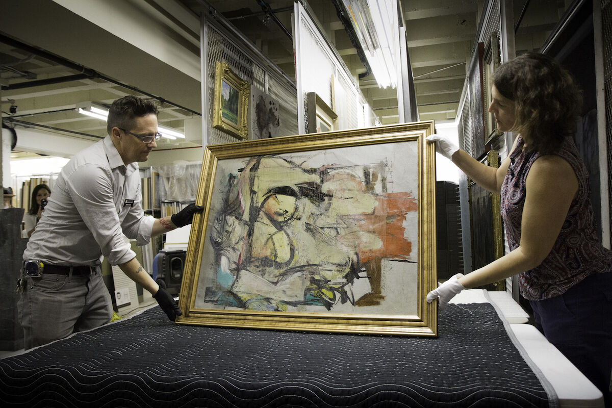 The recovered painting by Willem de Kooning is readied for examination by University of Arizona Museum of Art staff Nathan Saxton and Kristen Schmidt. Photo courtesy the University of Arizona Museum of Art.