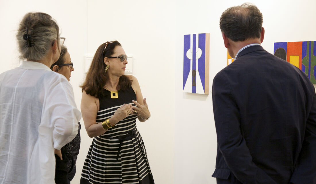 Karla Osorio (center, owner of Gabinete de Arte k2o, Brasília) discusses Galeno's colorful oil on wood compositions with collectors; Courtesy VOLTA13