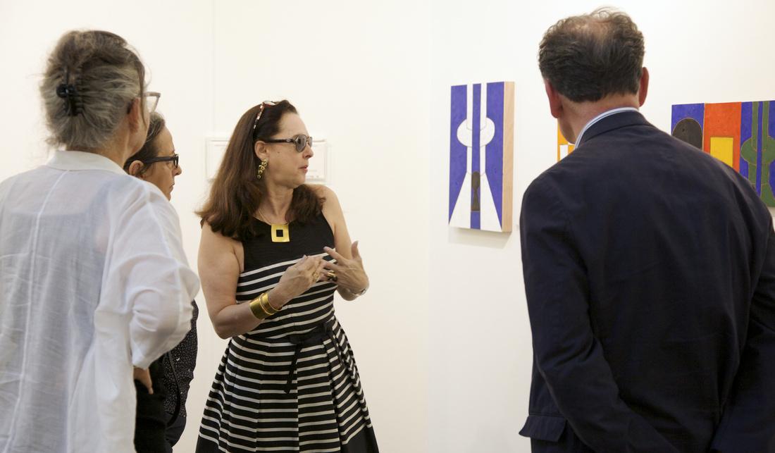 Karla Osorio (center, owner of Gabinete de Arte k2o, Brasília) discusses Galeno's colorful oil on wood compositions with collectors; Courtesy VOLTA13