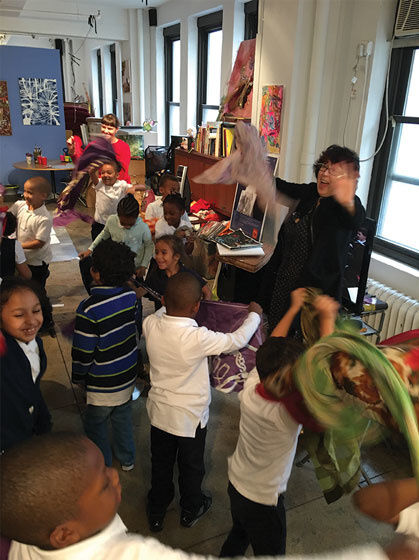 Cyndie Berthezene with Time In students at their 29th Street studio. Image courtesy of Time In Children's Arts Initiative.