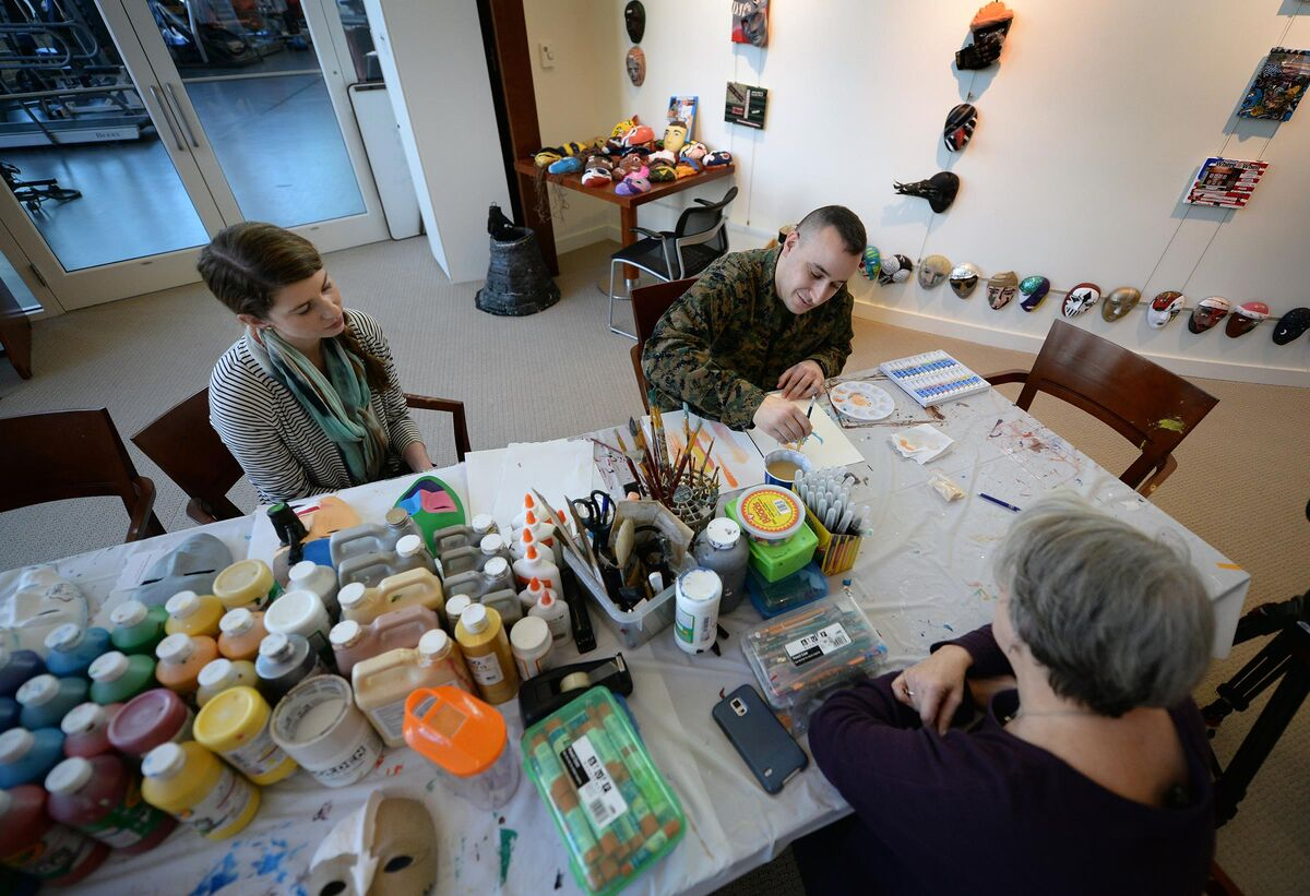 Marine Corps Staff Sgt. Anthony Mannino performs art therapy with guidance from Adrienne Stamper, art therapy intern as part of his traumatic brain injury treatment and recovery at the National Intrepid Center of Excellence in Bethesda, Md., March 1, 2016. Photo by Marvin Lynchard. Courtesy the United States Department of Defense.