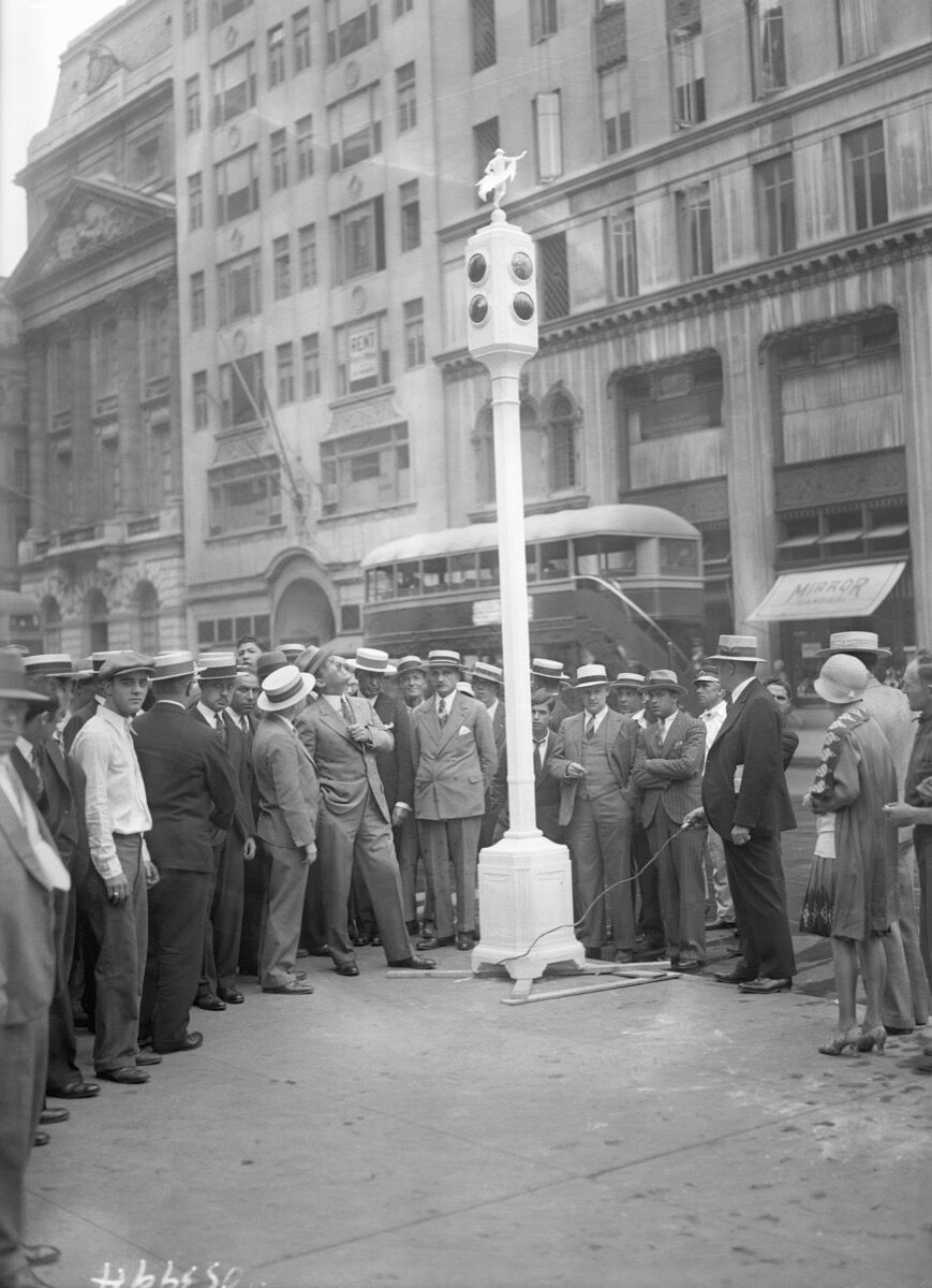 Photo of Commissioner Grover Whalen, along with a crowd of others, examining the new signal posts at 57th Street and 5th Avenue. Photo via Getty Images.