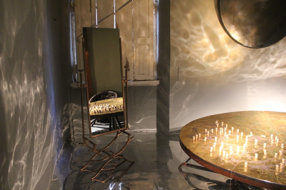 """The organic details of the """"8 Marzo"""" table by Carlo Trucchi reflected in Simon Ricart's mirror realized in pure copper and gold finishing. Courtesy Erastudio Apartment Gallery"""