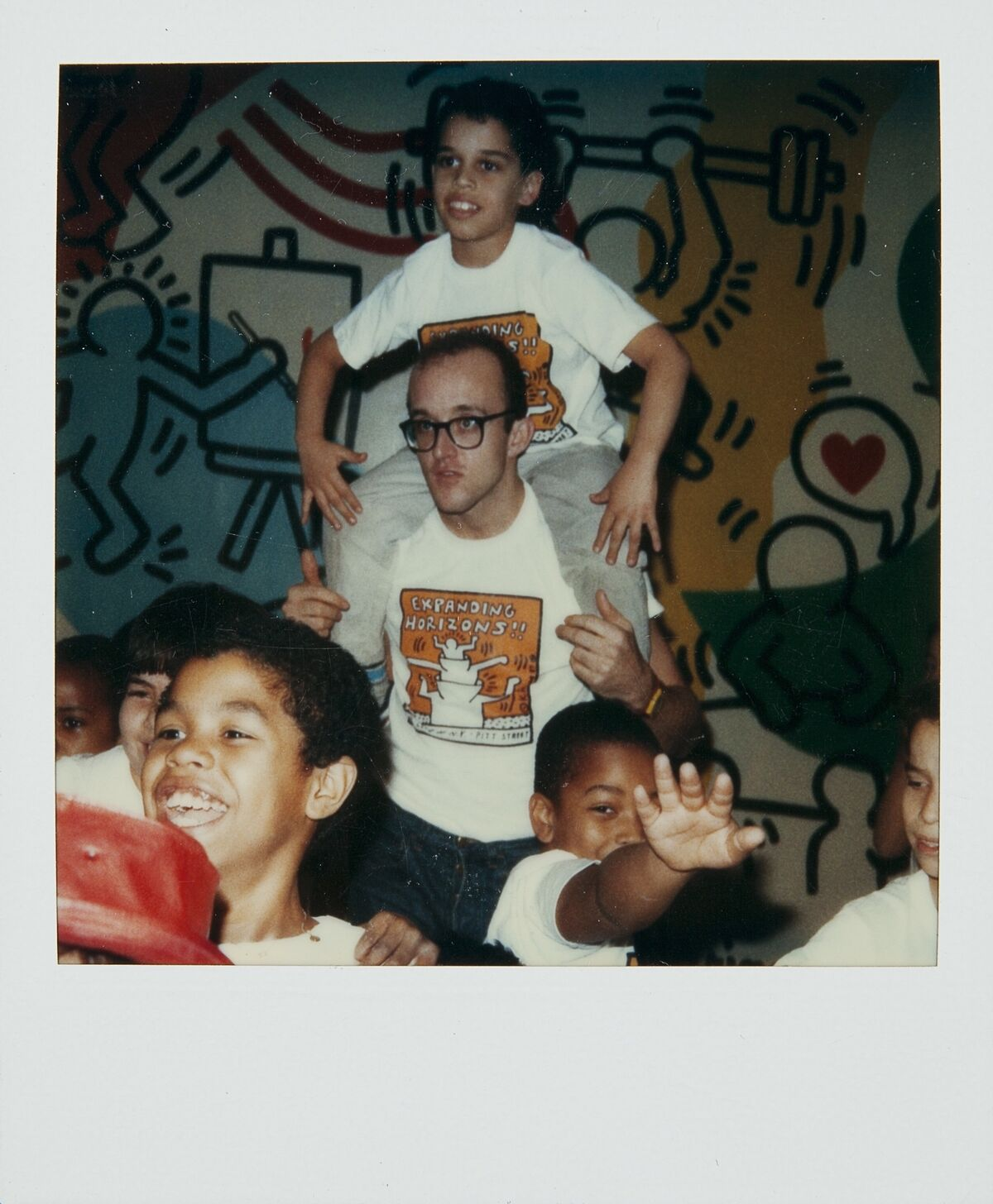 Polaroid of Keith Haring with members of the Boy's Club, Pitt Street, New York City, 1987. © Keith Haring Foundation. Courtesy of The Keith Haring Foundation Archives.