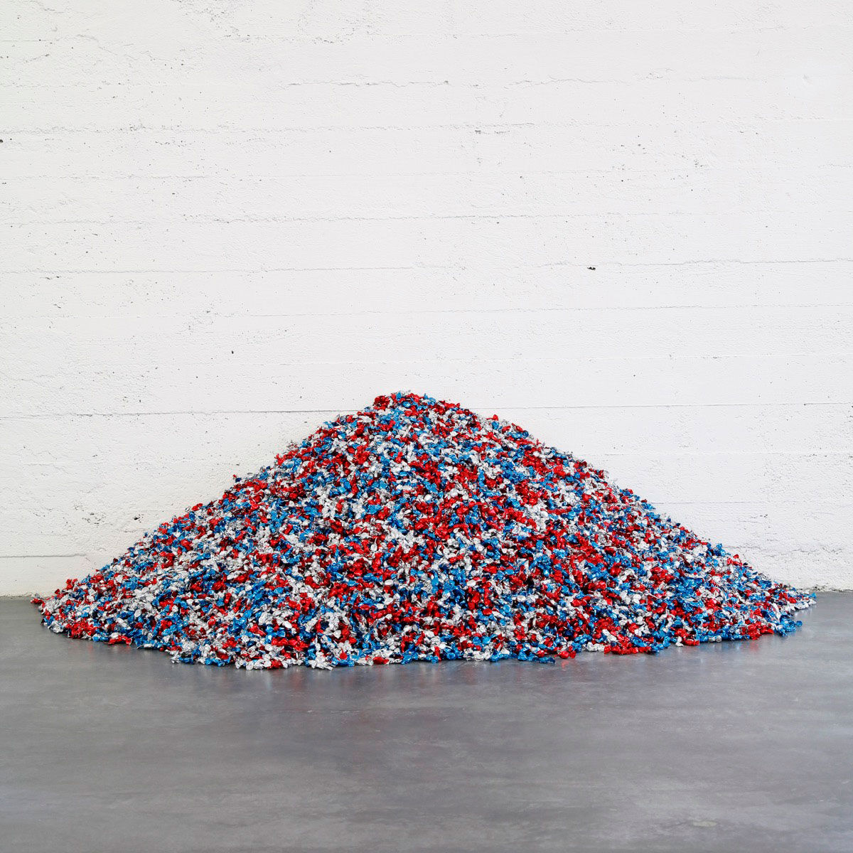 "Felix Gonzalez-Torres, ""Untitled"" (USA Today), 1990. Candies individually wrapped in red, silver, and blue cellophane, endless supply. Overall dimensions vary with installation. Ideal weight: 300 lbs. Installation view: Felix Gonzalez-Torres: Specific Objects without Specific Form. Wiels Contemporary Art Centre, Brussels, Belgium. 16 Jan. –  28 Feb. 2010. Cur. Elena Filipovic; 5 Mar. –  2 May 2010. Cur. Danh Vo. © The Felix Gonzalez-Torres Foundation. Courtesy of Andrea Rosen Gallery, New York."