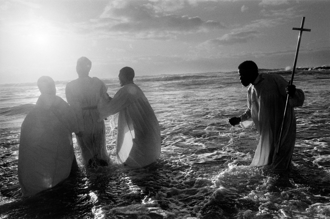 Abbas,Every Sunday, at dawn, priests of the Zion Church, from the Khayelitsha black township, take their newly converted congregation to the sea to be baptized through immersion. Cape Town, South Africa, 1999. © Abbas / Magnum Photos, courtesy ofArthur Ross Gallery, University of Pennsylvania.