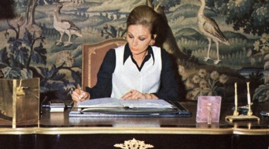 Farah Pahlavi, former empress of Iran, at work at her desk in the 1970s. Photo via Wikimedia Commons.