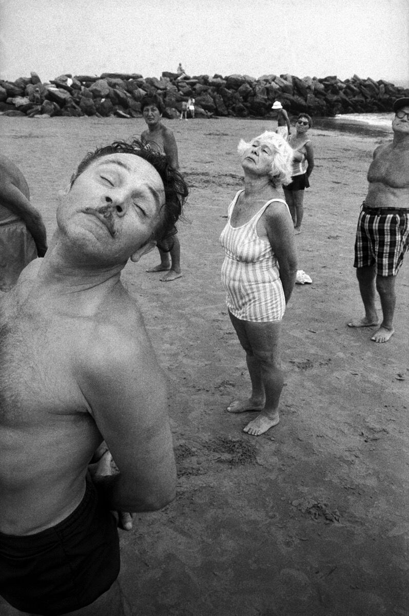 Bruce Gilden, Close-up of man exercising with a group of people on the beach, Coney Island, New York City, 1977. © Bruce Gilden/Magnum Photos. Courtesy of Magnum Photos.