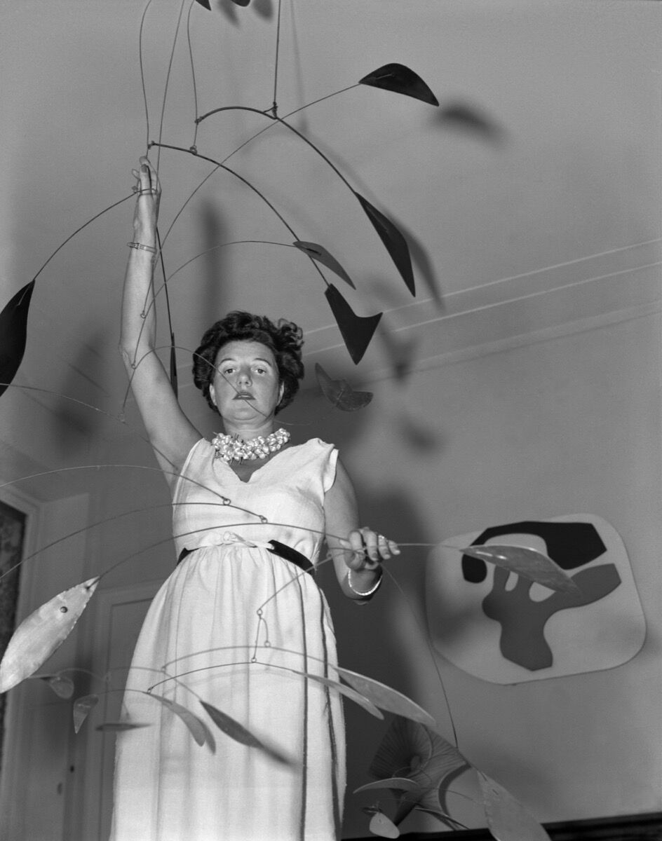 "Peggy Guggenheim with Alexander Calder's ""Arc of Petals."" Palazzo Venier dei Leoni, Venice, early '50s. © Fondazione Solomon R. Guggenheim, foto Archivio CameraphotoEpoche, donazione Cassa di Risparmio di Venezia, 2005. © 2017 Calder Foundation, New York / Artists Rights Society (ARS), New York."