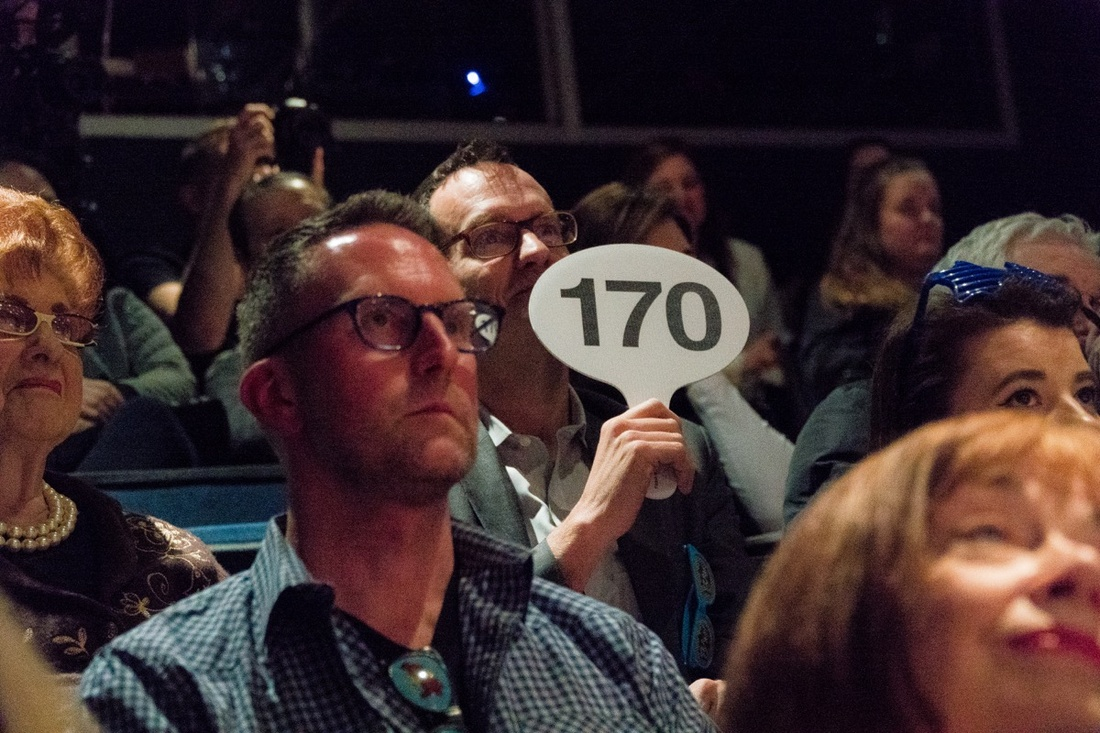 """Audience bidding at """"Beneath the Gavel"""" at 59E59 Theaters. Photo by Will Gangi."""