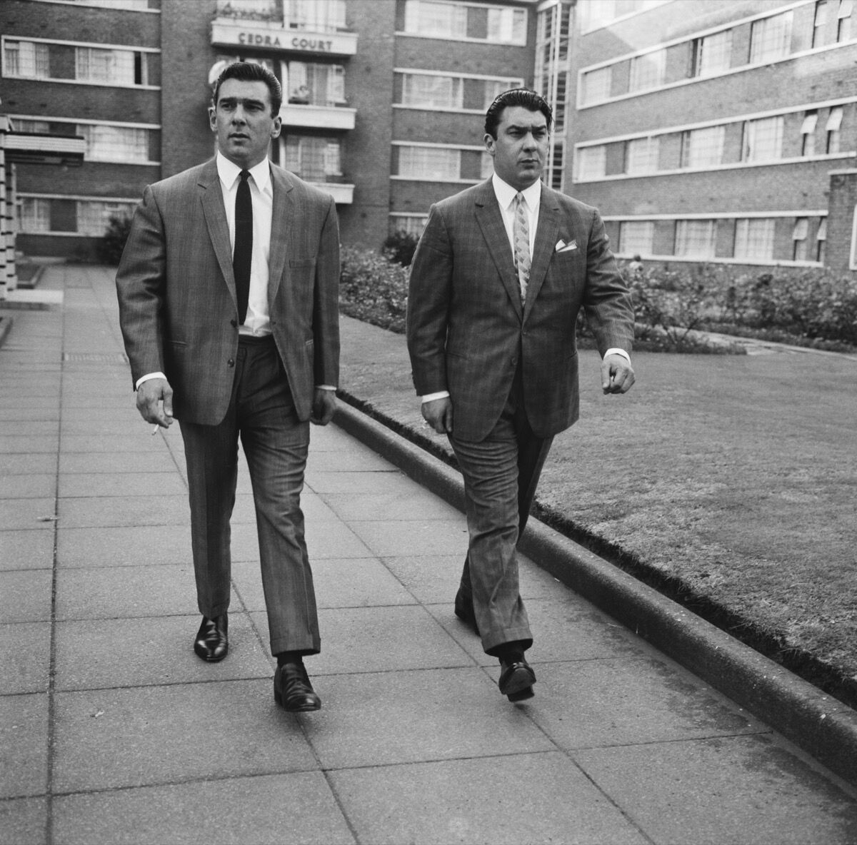 Twin brothers and organised crime bosses Ronnie and Reggie Kray in Cedra Court, off Cazenove Road in northeast London, 1964. Photo by Terry Disney/Express/Getty Images.