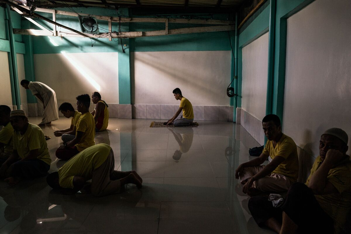 Men are seen saying their prayers inside a mosque in the Manila City Jail in Manila, Philippines, on October 31, 2018. In the Philippines, men with pending cases spend months, sometimes years, in overcrowded cells waiting to be charged, sentenced, or tried. Photo by Hannah Reyes Morales. Courtesy of the artist.