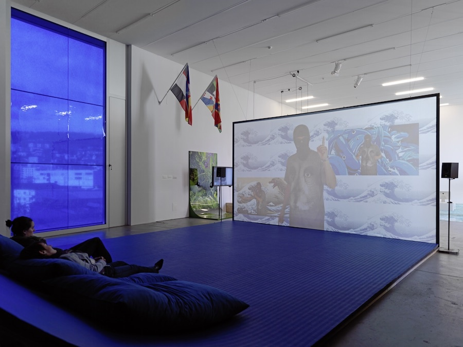 "Installation view of ""Filter Bubble,"" an 89plus exhibition co-­curated by Simon Castets and Hans Ulrich Obrist, at LUMA Westbau, Zürich, until February 14th,  2016. Photo by Stefan Altenburger. Pictured: Hito Steyerl, Liquidity Inc., 2014; James Bridle, Citizen Ex Flags 003 ­ 007, 2015; Ho Rui An, Screen Green, 2015."