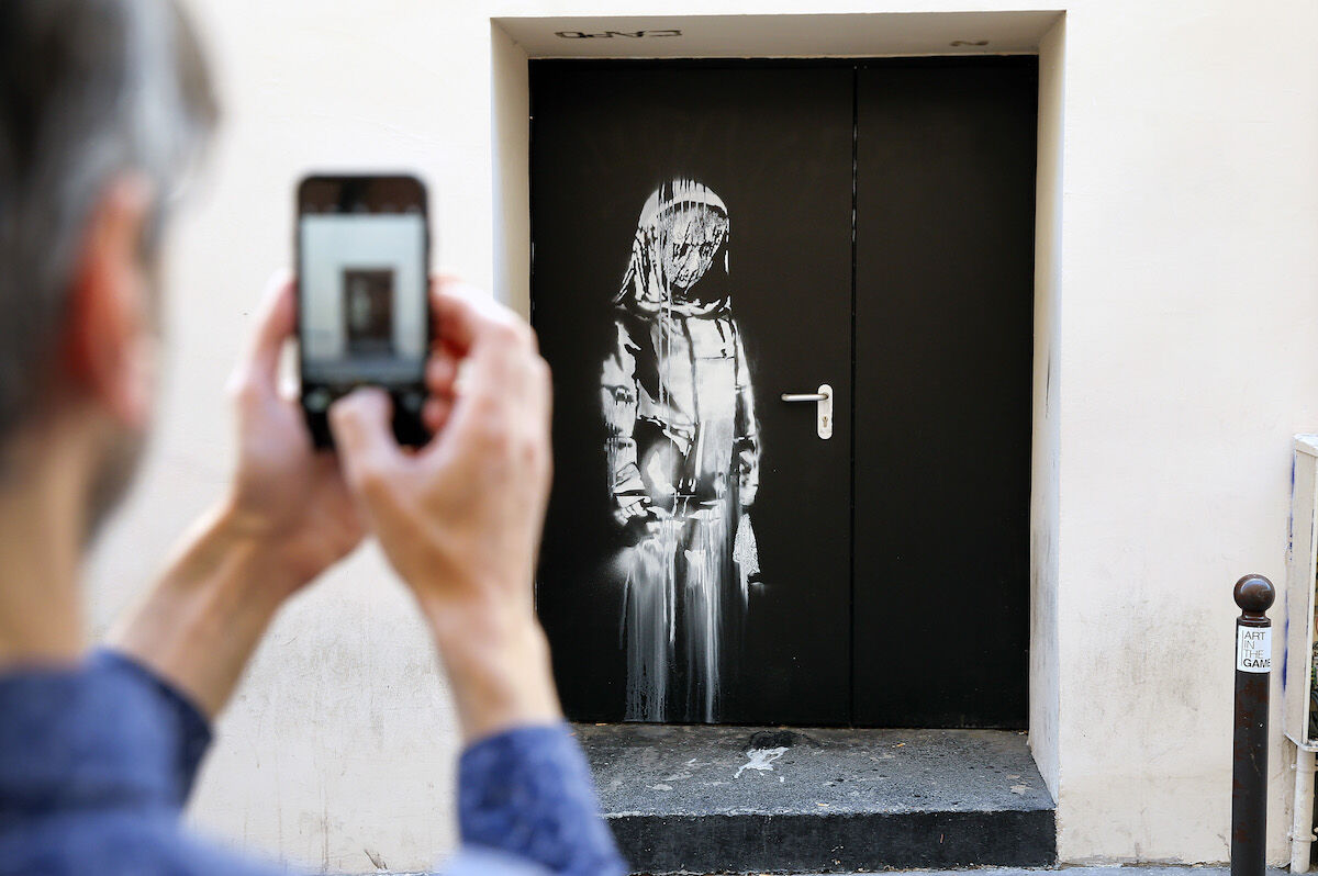 A man photographs the Banksy mural on one of the emergency doors at the Bataclan concert hall in Paris. Photo by  Chesnot/Getty Images.