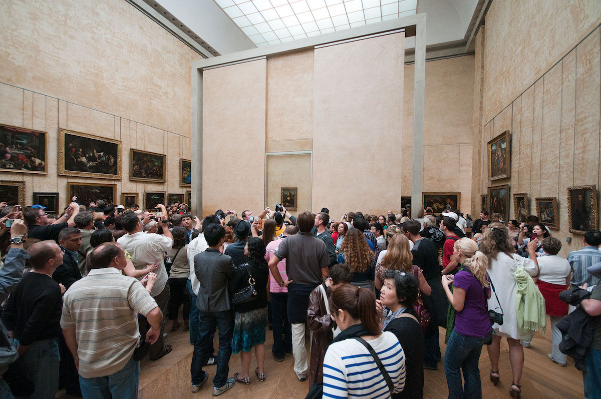 Visitors at the Louvre gather around the Leonardo da Vinci painting know as the Mona Lisa. Photo by Pueri Jason Scott, via Wikimedia Commo