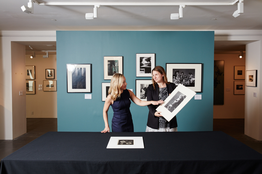 Worldwide Head of Photographs, Vanessa Hallett (right) holds up Dora Maar's Portrait de profil à la coiffure en hauteur with Head of Department, Sarah Krueger in conversation. Maar's work is featured in The Odyssey of Collecting. On table: Man Ray Rayograph, 1922.
