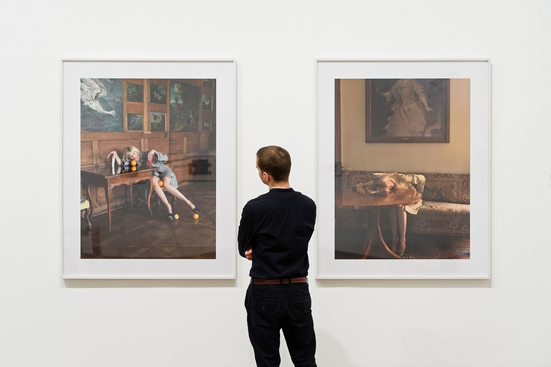 A man looks at artworks entitled 'Untitled (Claudia Schiffer series)' by Austrian artist Erwin Wurm, displayed at the 'Performing for the Camera' exhibition at the Tate Modern gallery in London on February 16, 2016. Photo by LEON NEAL/AFP/Getty Images.