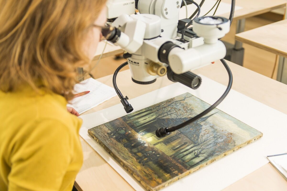 Restorer Kathrin Pilz researches Congregation Leaving the Reformed Church in Nuenen under the microscope. Photo: Jan-Kees Steenman. Courtesy of the Van Gogh Museum.