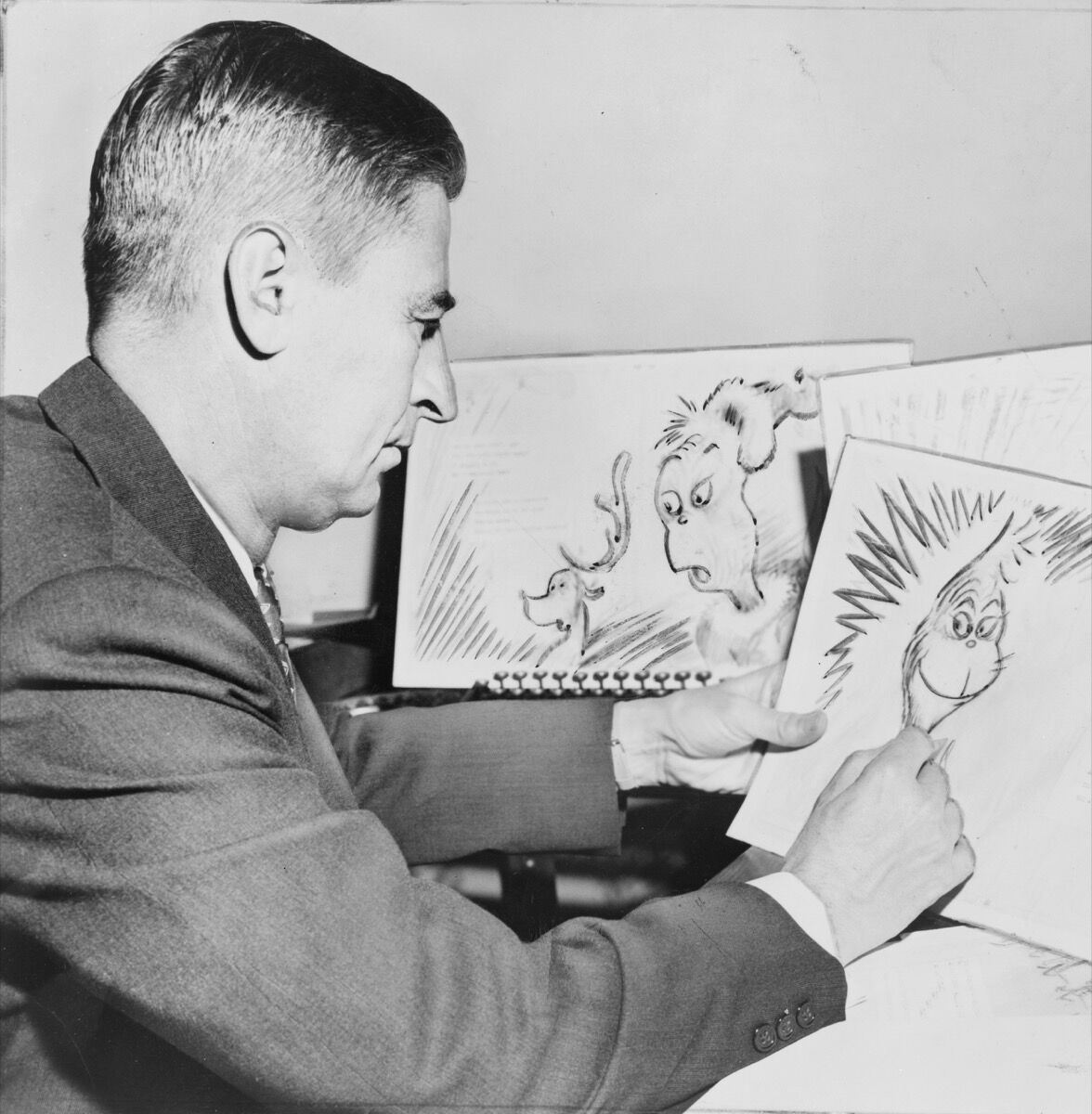 "Ted Geisel, American writer and cartoonist, at work on a drawing of the grinch for ""How the Grinch Stole Christmas,"" 1957. Photo by Al Ravenna. Source: Library of Congress. New York World-Telegram & Sun Collection."