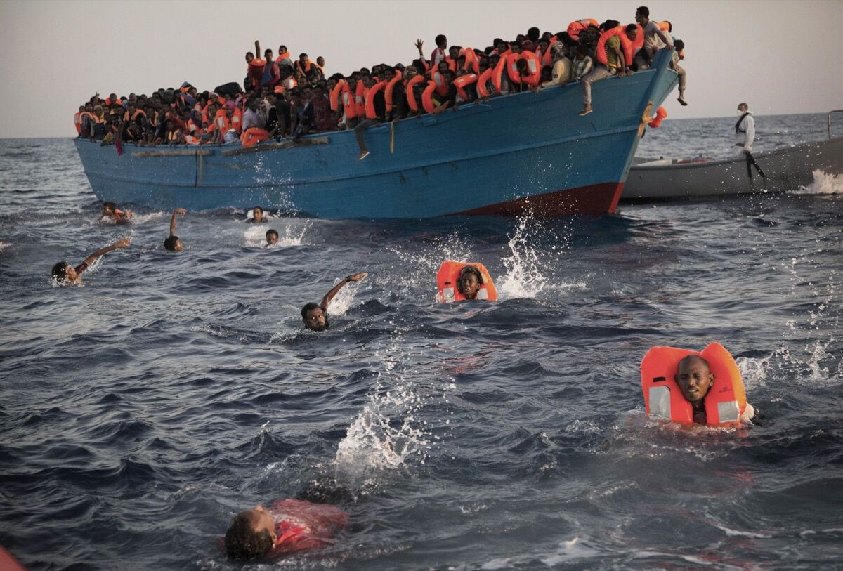 Migrants, most from Eritrea, jump into the water from a crowded wooden boat as they are helped by members of an NGO during a rescue operation in the Mediterranean sea, about 13 miles north of Sabratha, Libya, Monday, Aug. 29, 2016. Thousands were rescued Monday morning from more than 20 boats by members of the Proactiva Open Arms NGO before transferring them to the Italian coast guard and other NGO vessels operating in the zone. (AP Photo/Emilio Morenatti)