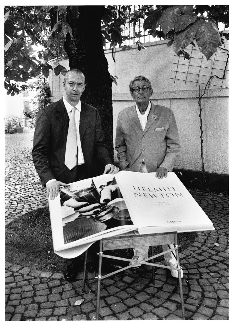 Helmut Newton, Benedikt Taschen and SUMO on its table designed by Philippe Starck, Cologne, July 7, 1999. Photo: Alice Springs. Courtesy TASCHEN.