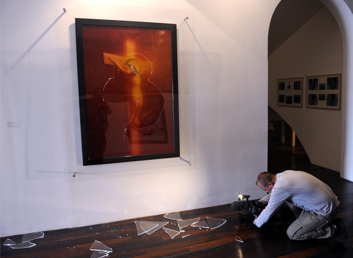 A cameraman films broken piece of glass from Andres Serrano's Immersion Piss Christ after its partial destruction by two catholic activists, Avignon, 2011. Photo by Boris Horvat/AFP/Getty Images.