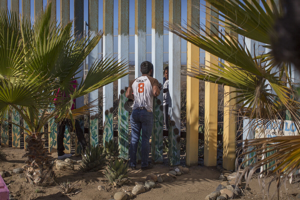 "A young man speaks to his family member through the border fence at Friendship Park, a meeting place on the border between Tijuana, Mexico and San Diego, California. For many families separated by immigration status, it is the only way that they can see their loved ones in person. Photo by Griselda San Martin from her series ""The Wall.""Courtesy of the artist."