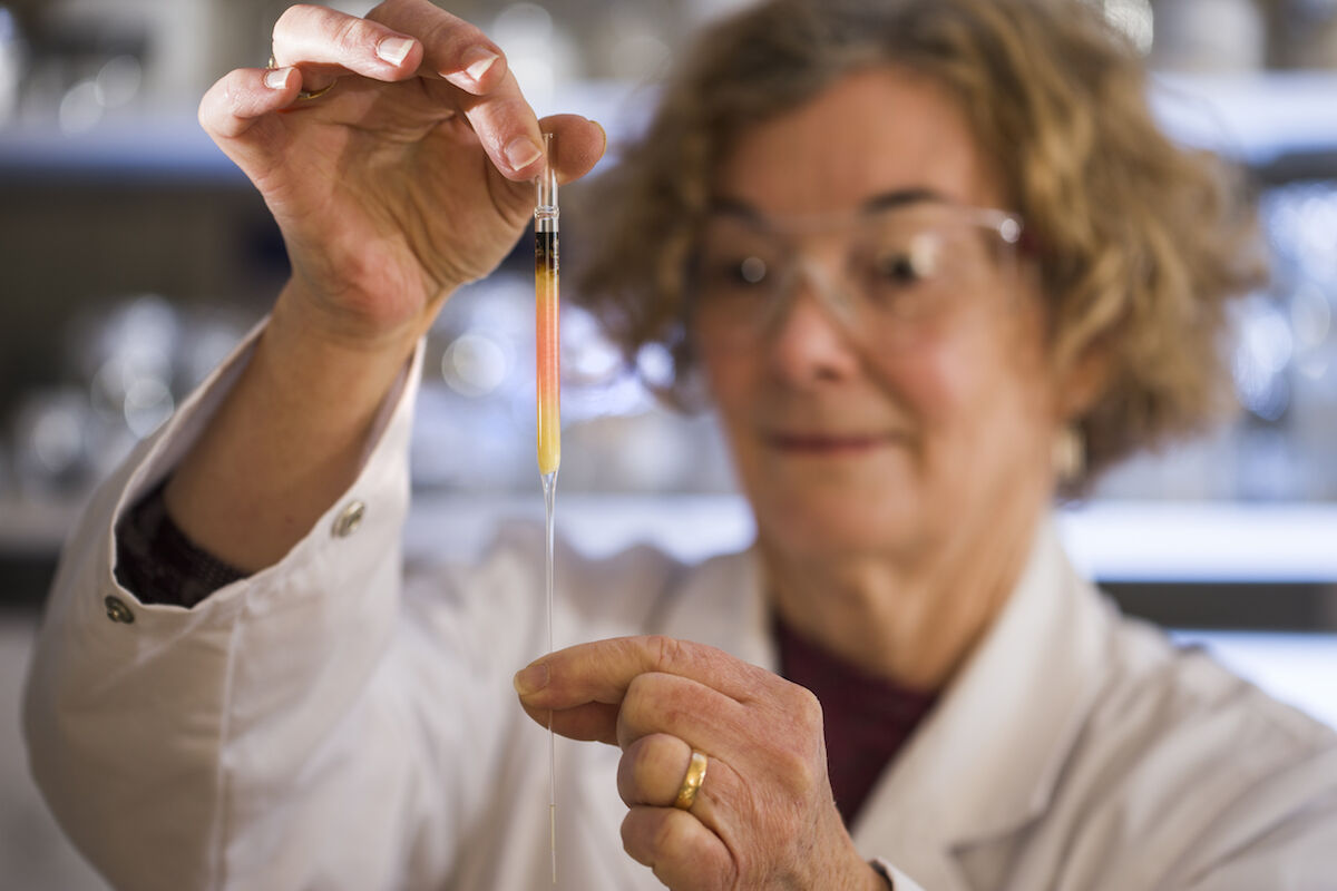 Biogeochemistry Lab Manager Janet Hope from the Australia National University Research School of Earth Sciences holds a vial of pink-colored porphyrins representing the oldest intact pigments in the world. Photo courtesy the Australian National University.