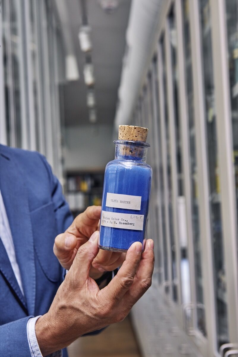 Narayan Khandekar holds up a bottle of synthetic ultramarine pigment. Photo by Tony Luong for Artsy.