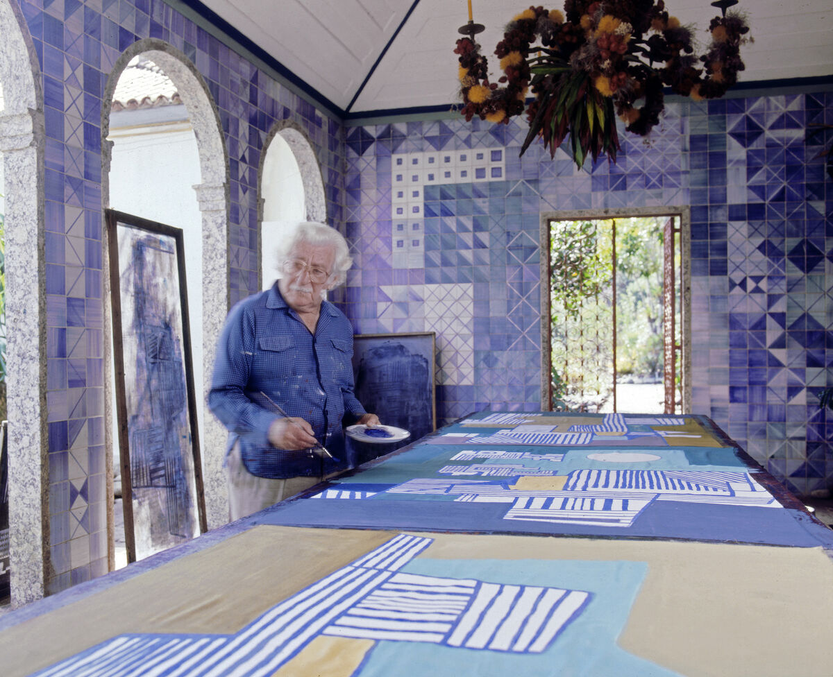 Roberto Burle Marx painting a tablecloth in the loggia of his home, 1980s; the azulejo tile walls and chandelier composed of fruit and flowers on a metal armature are his work. Photo © Tyba.