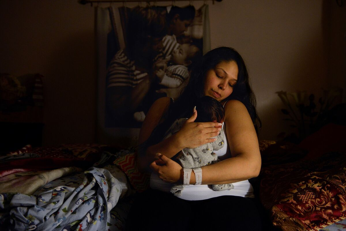 Bianca Castillo cradles her newborn son, Eliseo, on March 21, 2018 in Fort Worth, Texas. Behind her hangs a photo blanket of Ama holding her other great-grandson, Jack, when he was a newborn.  Photo by Desiree Rios. Courtesy of the artist.