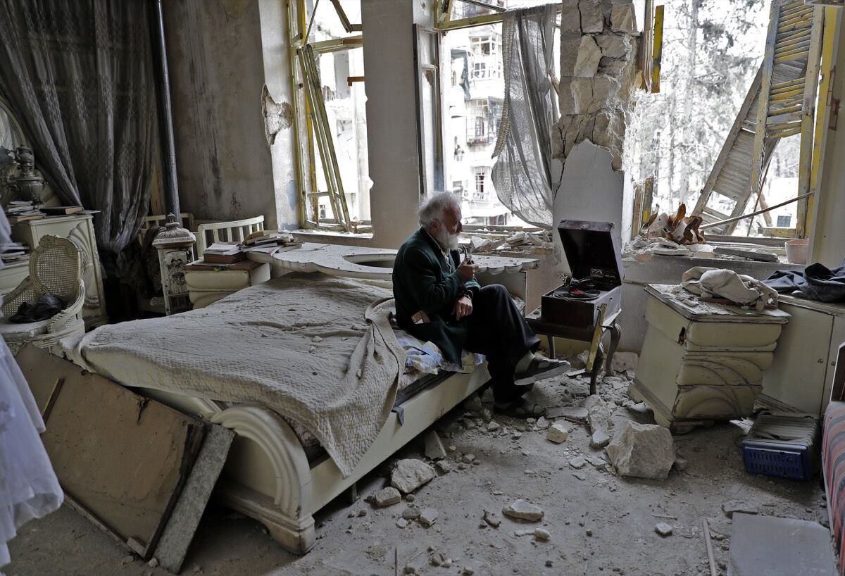 Mohammed Mohiedin Anis, or Abu Omar, 70, smokes his pipe as he sits in his destroyed bedroom listening to music on his vinyl player, gramophone, in Aleppo's formerly rebel-held al-Shaar neighbourhood. / AFP PHOTO / JOSEPH EID (Photo credit should read JOSEPH EID/AFP/Getty Images)