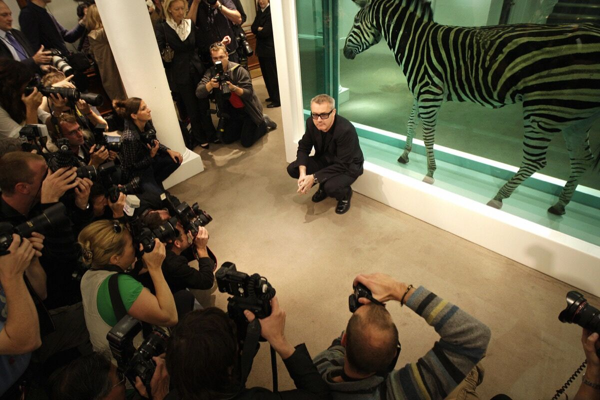 Damien Hirst poses with his work The Incredible Journey at Sotheby's art gallery and auction house in London on September 8, 2008. Photo by SHAUN CURRY/AFP/Getty Images.