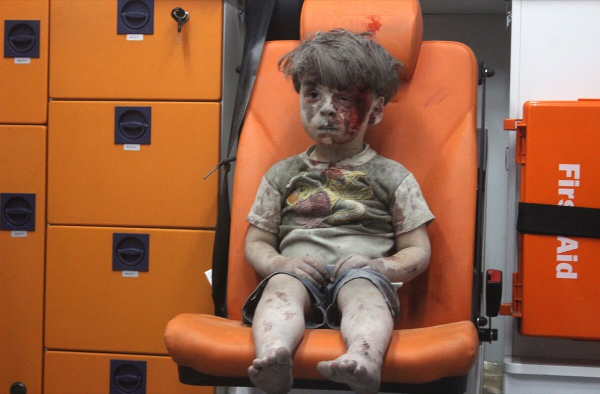 ALEPPO, SYRIA - AUGUST 17: (EDITORS NOTE: Image contains graphic content.) 5-year-old wounded Syrian kid Omran Daqneesh sits alone in the back of the ambulance after he got injured during Russian or Assad regime forces air strike targeting the Qaterji neighbourhood of Aleppo on August 17, 2016. (Photo by Mahmoud Raslan/Anadolu Agency/Getty Images)