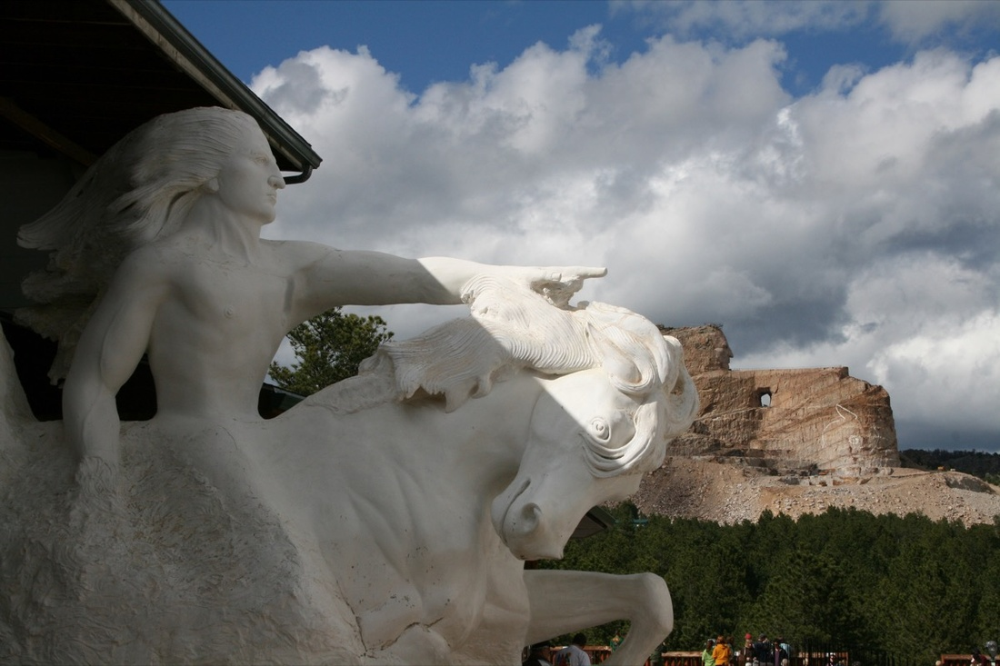 Photo of Crazy Horse Memorial, with Mount Rushmore in the background, by Kari, via Flickr.
