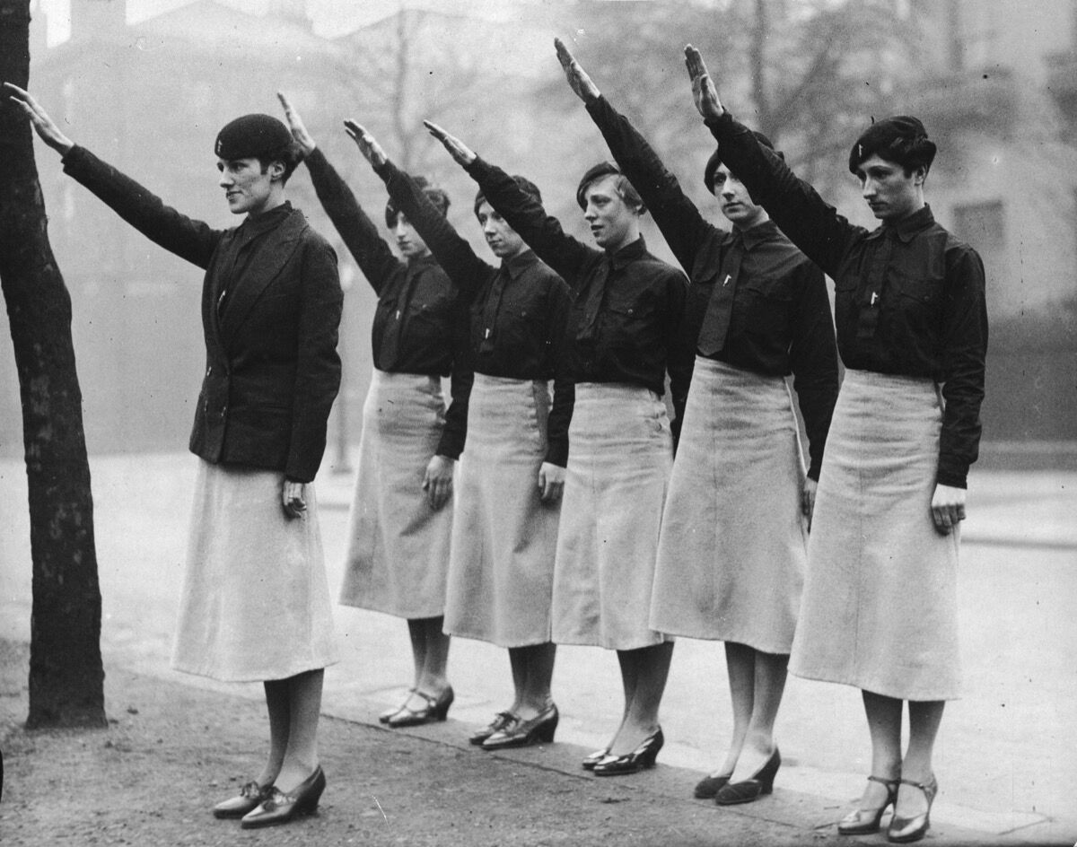 """Women """"black-shirts"""" from Sir Oswald Mosley's British Union of Fascists on parade in Liverpool give the fascist salute. Photo by Fox Photos/Getty Images."""
