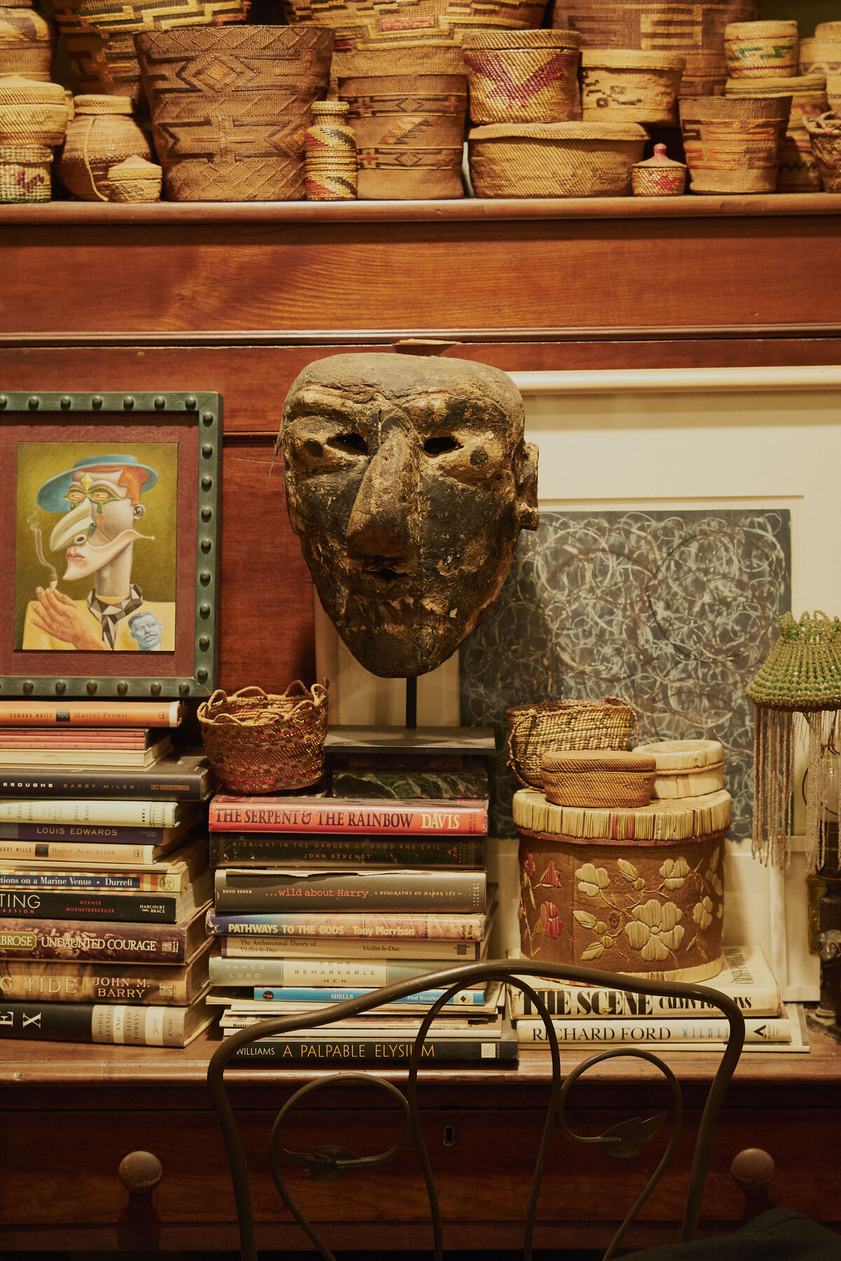 A character mask from the Michoacán state of Mexico rests on a perch of literature in Fagaly's living room, adorned with a collection of baskets by Indigenous peoples from the Northwest Coast, spanning Oregon, Washington, and British Columbia. Photo by Michael Adno for Artsy.